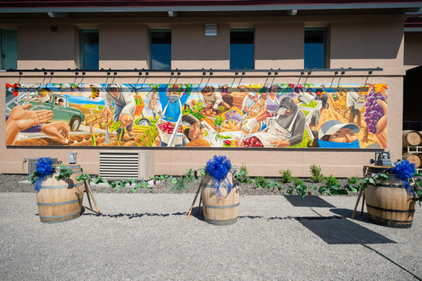 Latino Heritage Mural panel behind ceremonial ribbon cuttin vine.