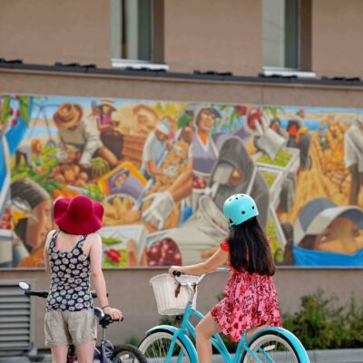 Bicyclists stop to view the Mid-Columbia Latino Heritage Mural at Columbia Gardens.