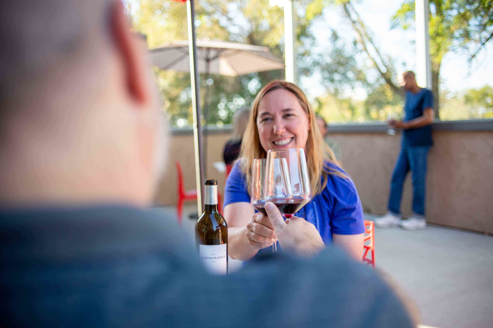 A couple raises their glasses for a toast at Bartholomew Winery's outdoor patio.