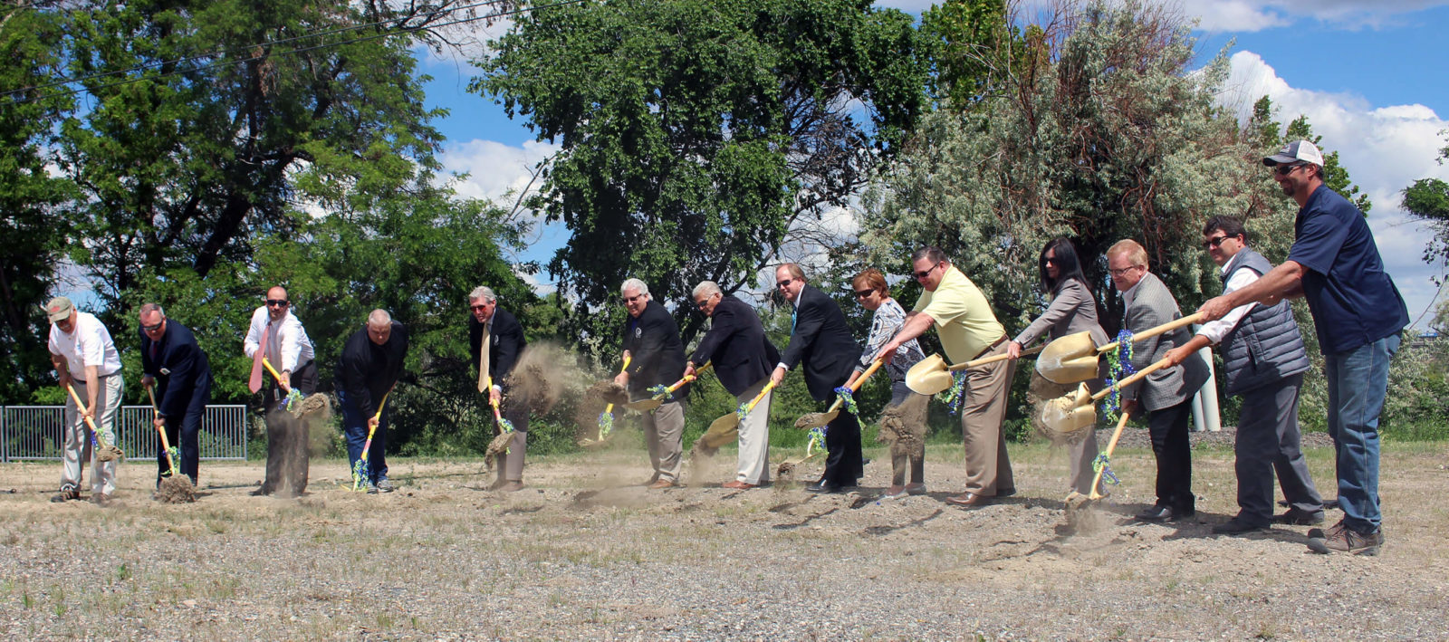 Fourteen people turn dirt at groundbreaking ceremony.