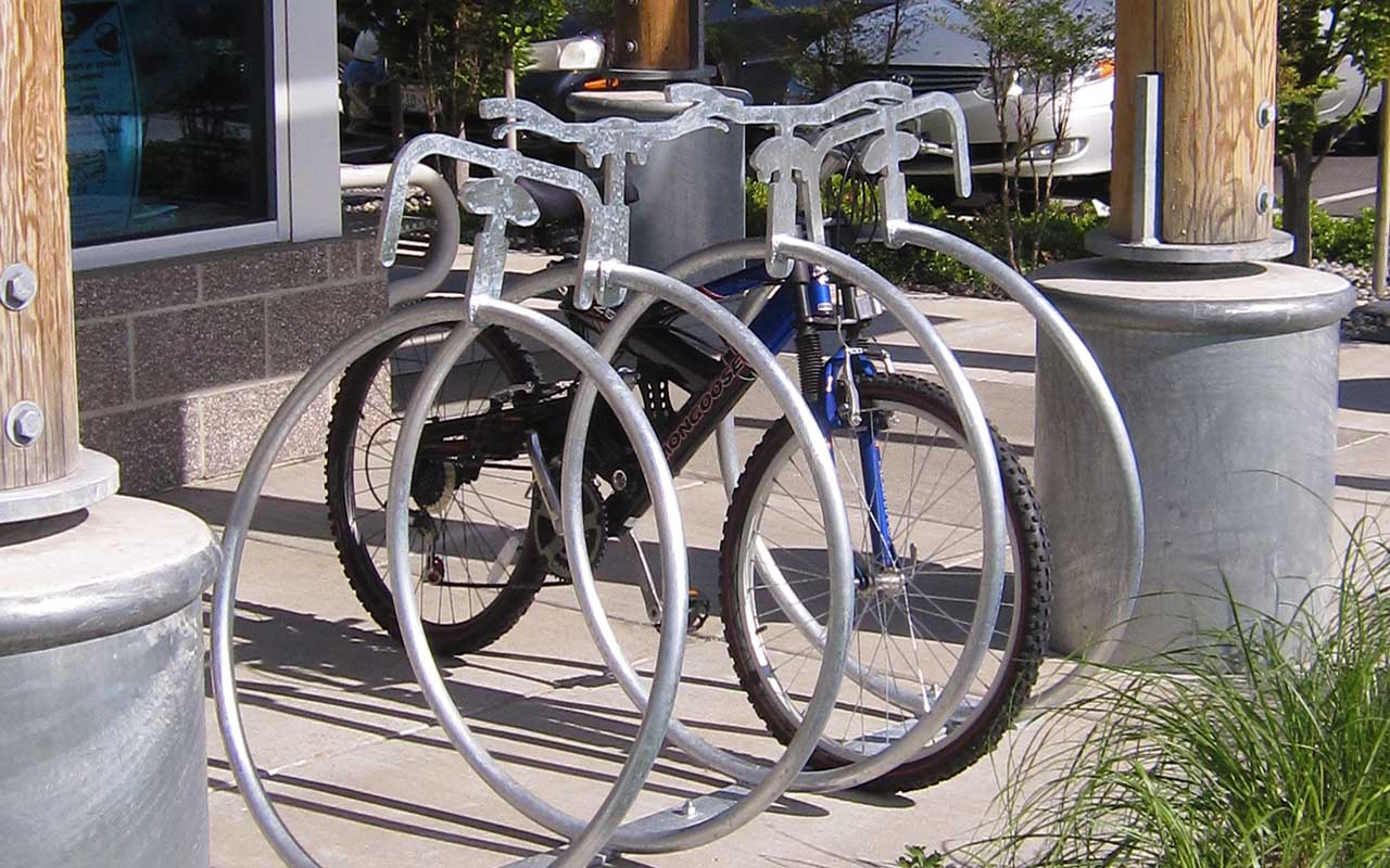 Bicycle chained to artistic bicycle-shaped rack.