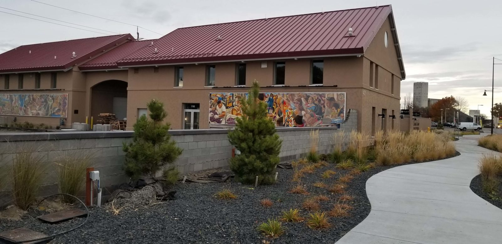 Two Columbia Gardens buildings, sidewalk, landscaping and murals.