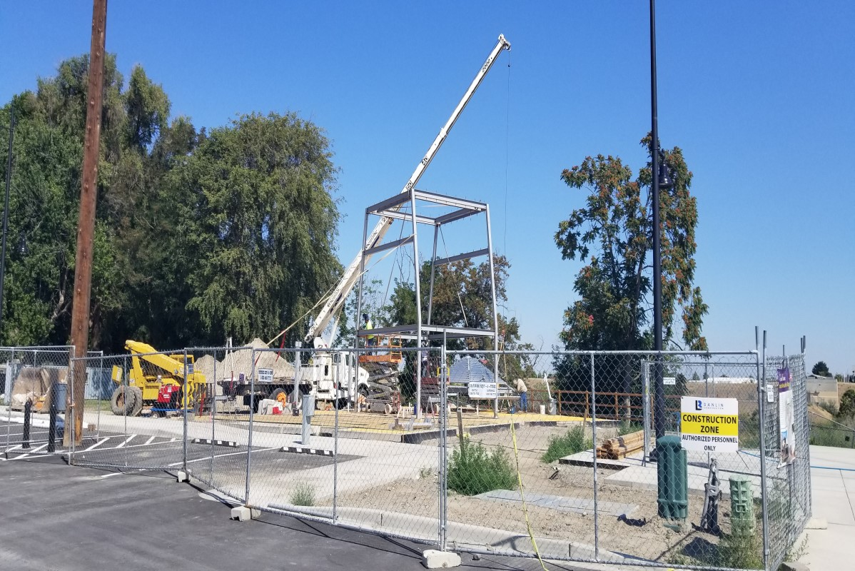 Construction crews use crane to install clock tower framework.