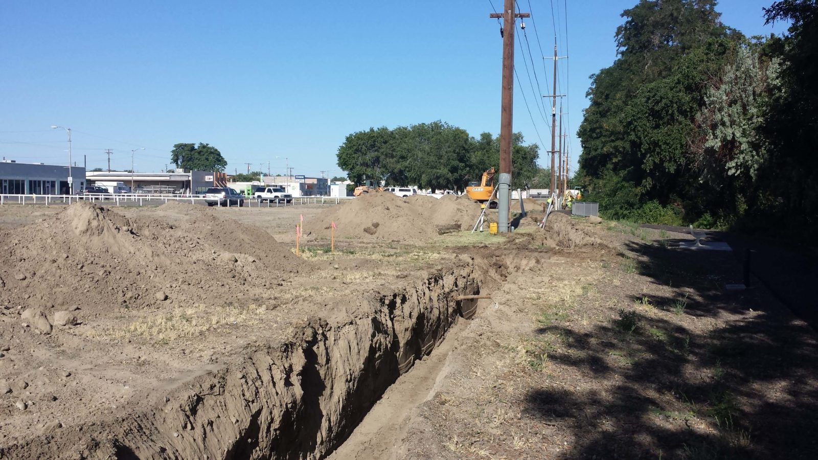 Open utility trench underneath power lines.