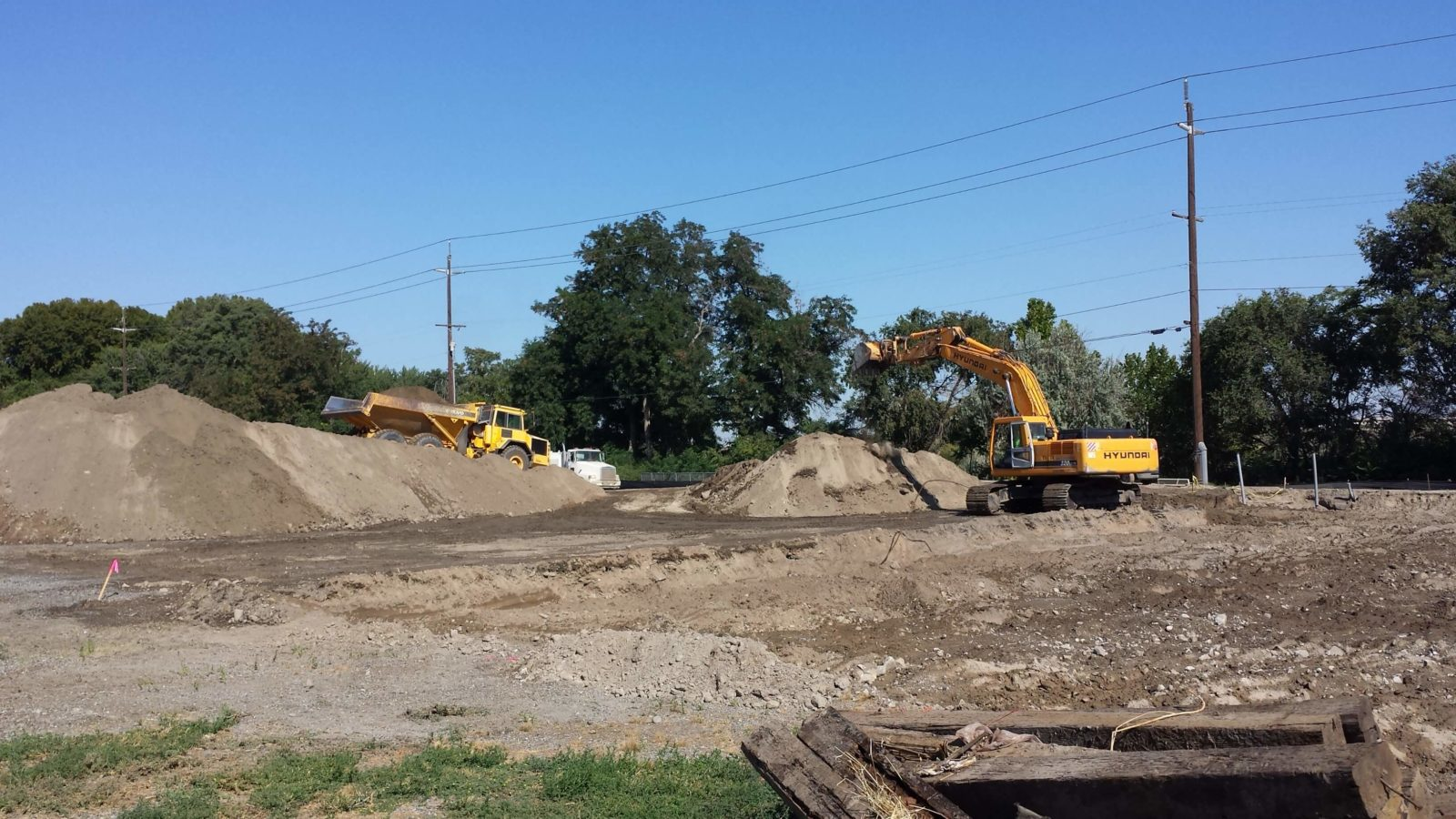 Heavy equipment moving dirt into piles.