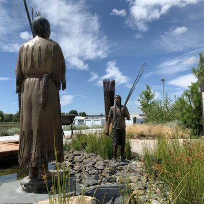 Two bronze statues with Tule reeds at The Gathering Place.