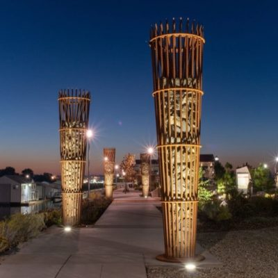 """The Gathering Place Sapáxikas """"Willow Fish Traps"""" structures at night."""