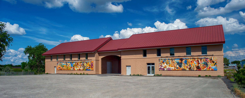 Latino Heritage Mural panels hanging on wine buildings.