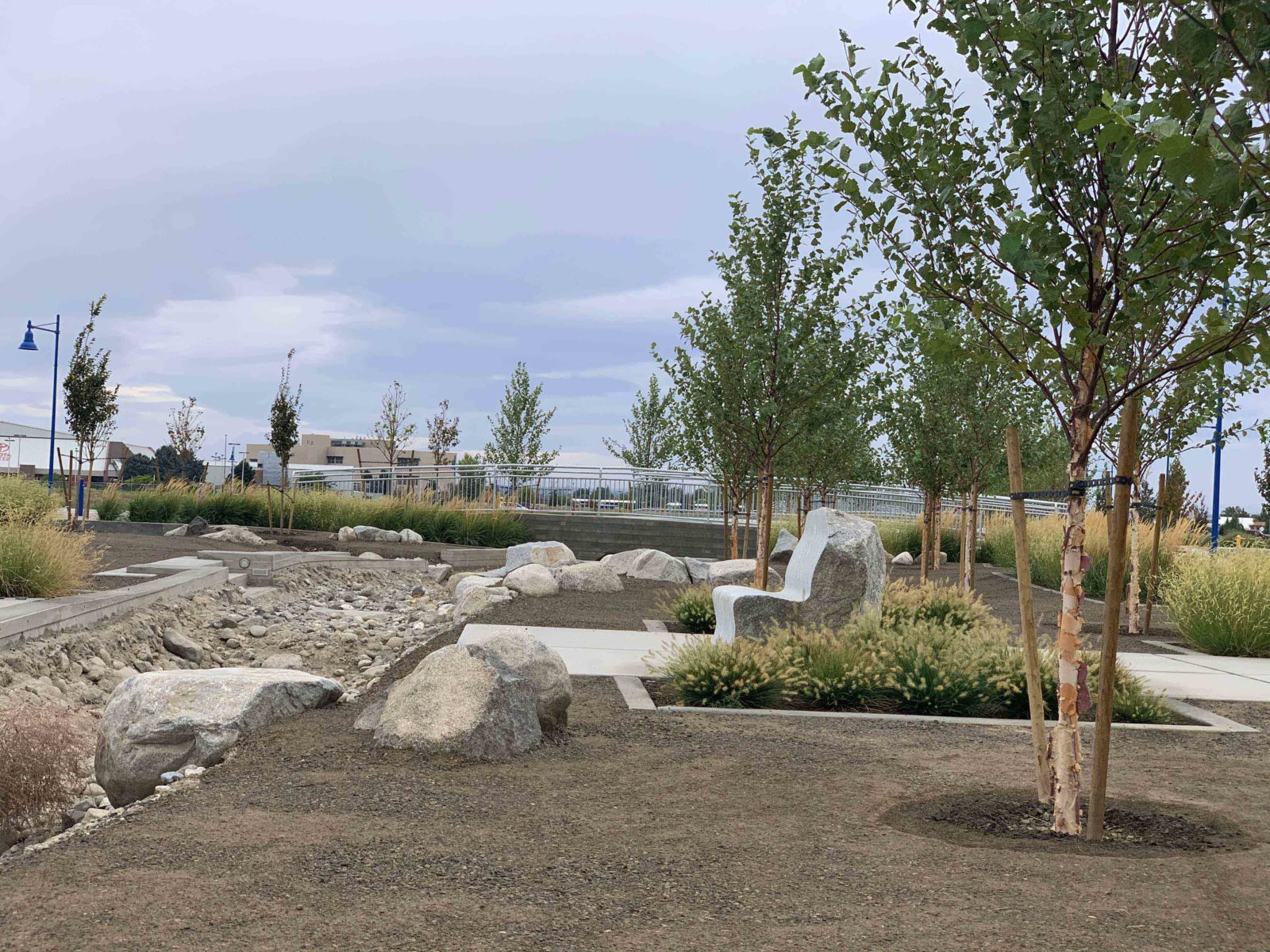 Trees, water feature, bench and bridge at Vista Field - phase one redevelopment.
