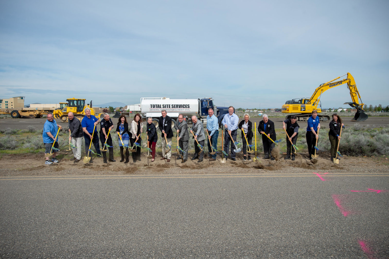 17 people break ground with construction equipment in background.