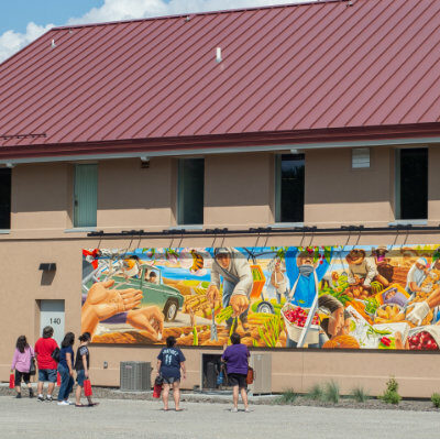 People looking at the Mid-Columbia Latino Heritage Mural at Columbia Gardens.