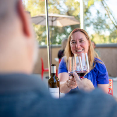 Friends enjoying wine on an outdoor tasting room patio at Columbia Gardens.