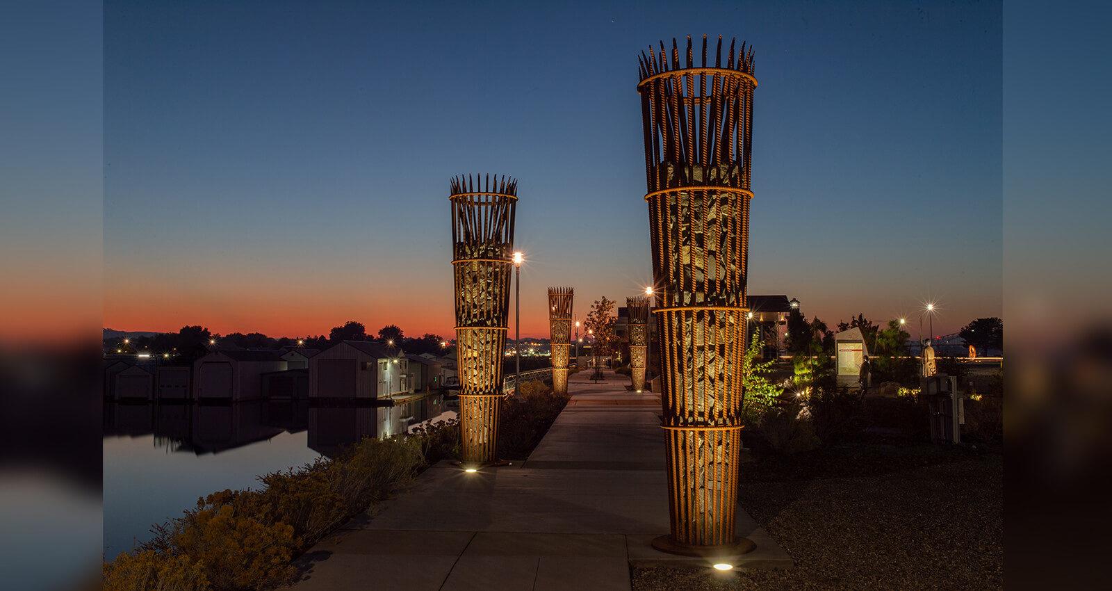 "Spotlights illuminate the Sapáxikas ""Willow Fish Traps"" artwork structures."