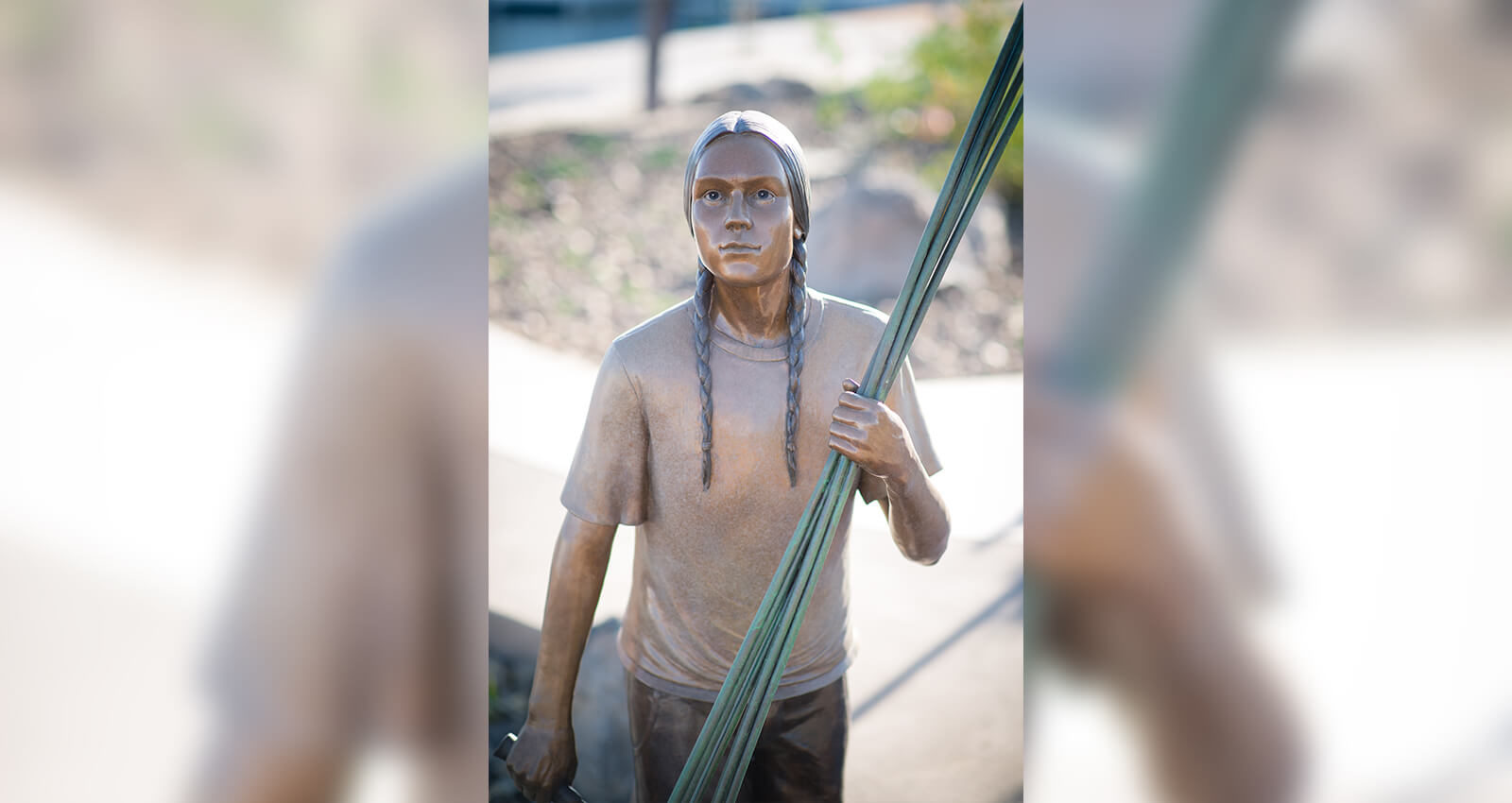 The Gathering Place Young Man sculpture holding tule reeds.
